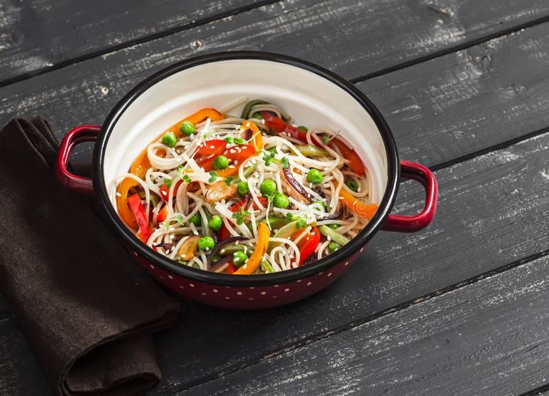 De groente beweegt gebraden gerecht en rijstnoedels in een emailkom op een donkere houten achtergrond royalty-vrije stock afbeelding