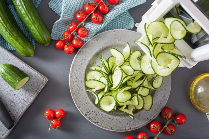 De groente van de Spiralizingskomkommer met spiralizer stock afbeelding