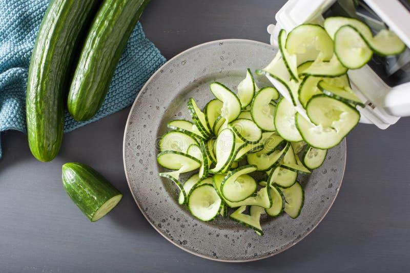 De groente van de Spiralizingskomkommer met spiralizer stock afbeeldingen