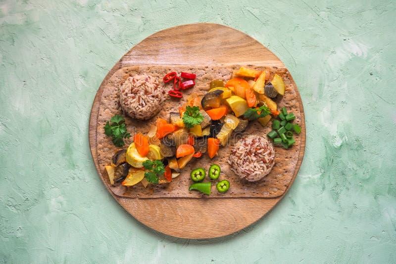 De groente versiert van gestoofde groenten en wilde rijst op een rond hakbord Gezond vegetarisch voedsel stock foto