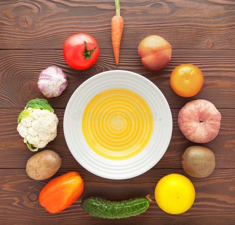 De groenten en de vruchten liggen rond een lege plaat op een houten lijst royalty-vrije stock foto
