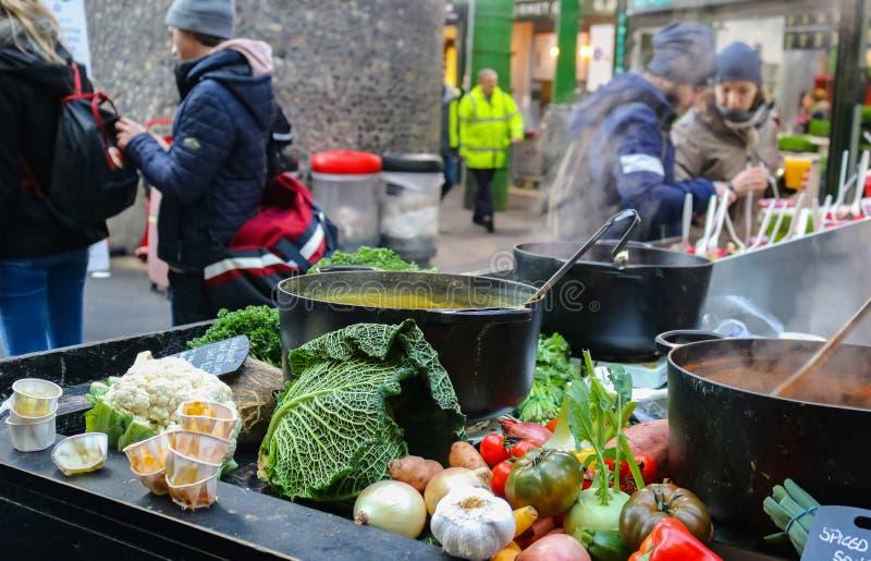 De groenten stapelden zich omhoog rond gietijzer het koken pottenhoogtepunt op van het stomen van soep aangezien de klanten zich  stock foto's