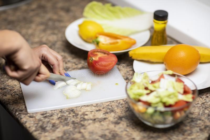 De groenten van handbesnoeiingen voor salade in de keuken stock foto