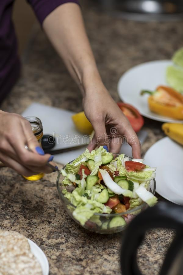 De groenten van handbesnoeiingen voor salade in de keuken stock afbeelding