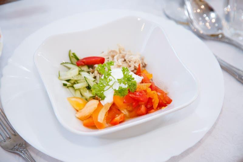 De groenten worden prachtig gesneden op een witte vierkante schotel Komkommer, rode tomaat, rode groene paprika, borst van kip en royalty-vrije stock foto