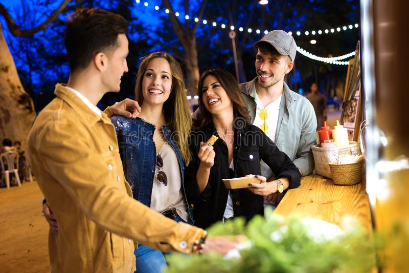 De groep aantrekkelijke jonge en vrienden die eet markt in de straat spreken bezoeken royalty-vrije stock fotografie