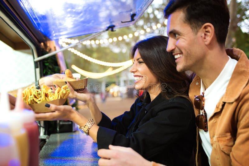 De groep aantrekkelijke jonge vrienden die en verschillende types van snel voedsel kiezen kopen eet binnen markt in de straat stock afbeeldingen