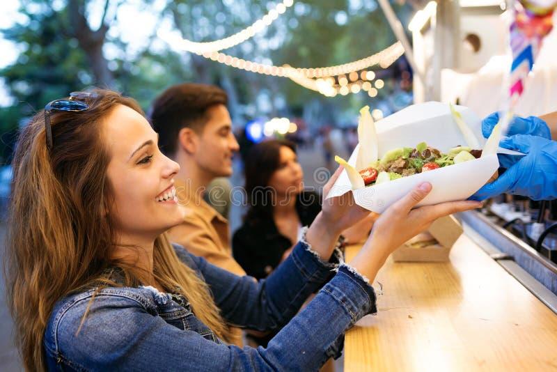 De groep aantrekkelijke jonge vrienden die en verschillende types van snel voedsel kiezen kopen eet binnen markt in de straat royalty-vrije stock foto