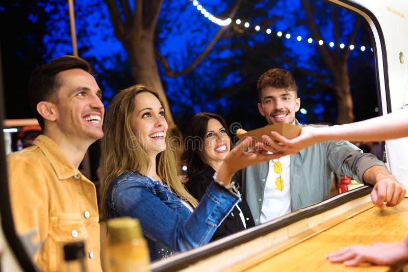 De groep aantrekkelijke jonge vrienden die en verschillende types van snel voedsel kiezen kopen eet binnen markt in de straat stock afbeelding