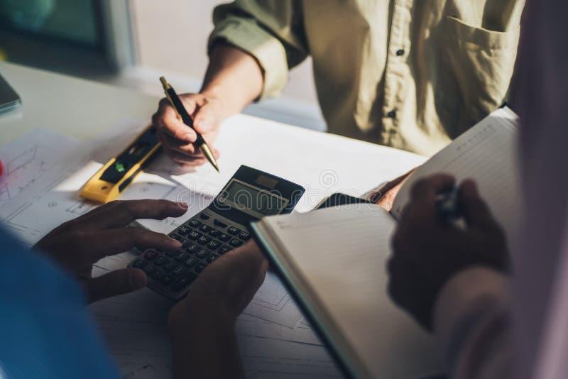 De groep architecten die en calculator bespreken gebruiken berekent ongeveer de kosten met binnen voor het werk het project van h stock afbeelding