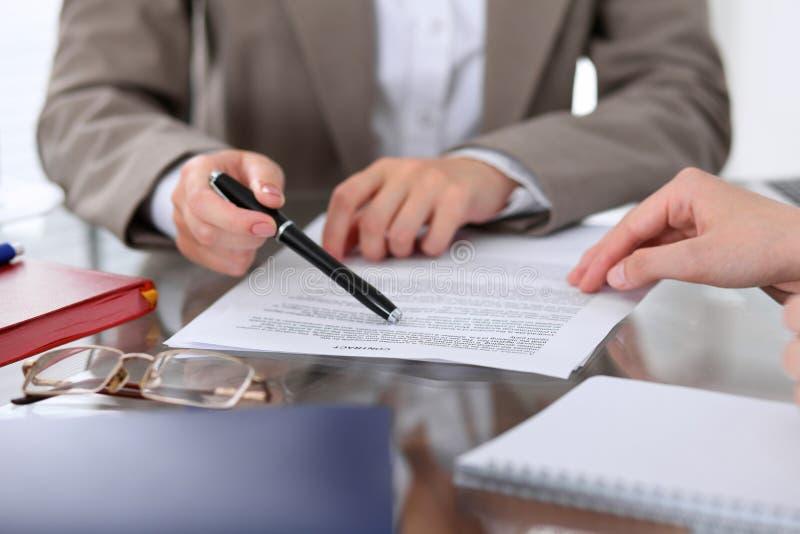 De groep bedrijfsmensen en advocaten die contractdocumenten bespreken die bij de lijst zitten, sluit omhoog royalty-vrije stock foto's