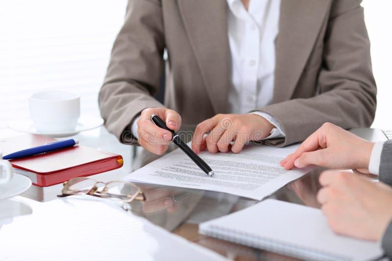 De groep bedrijfsmensen en advocaten die contractdocumenten bespreken die bij de lijst zitten, sluit omhoog stock foto's