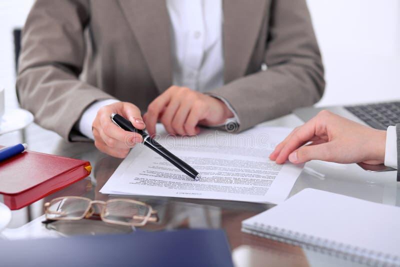 De groep bedrijfsmensen en advocaten die contractdocumenten bespreken die bij de lijst zitten, sluit omhoog stock afbeelding