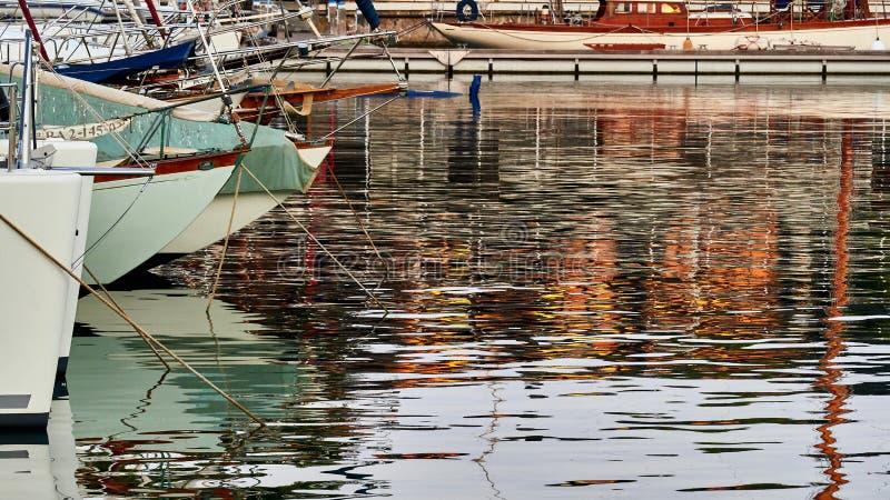 De groep boten parkeerde in de Haven Vell van Barcelona, bij zonsondergang, met oranje lichten die in het water nadenken stock foto