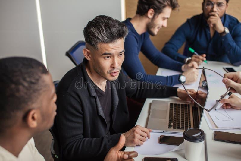 De groep concentreerde mannelijke bedrijfsmensen verzamelde zich rond computer in bureau het spreken royalty-vrije stock foto