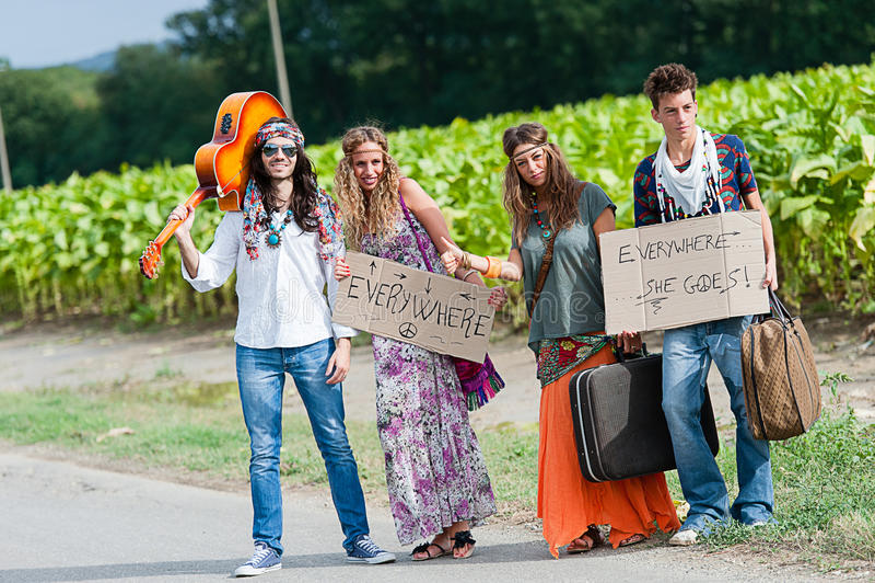 De Groep die van de hippie op een Weg van het Platteland liften stock foto