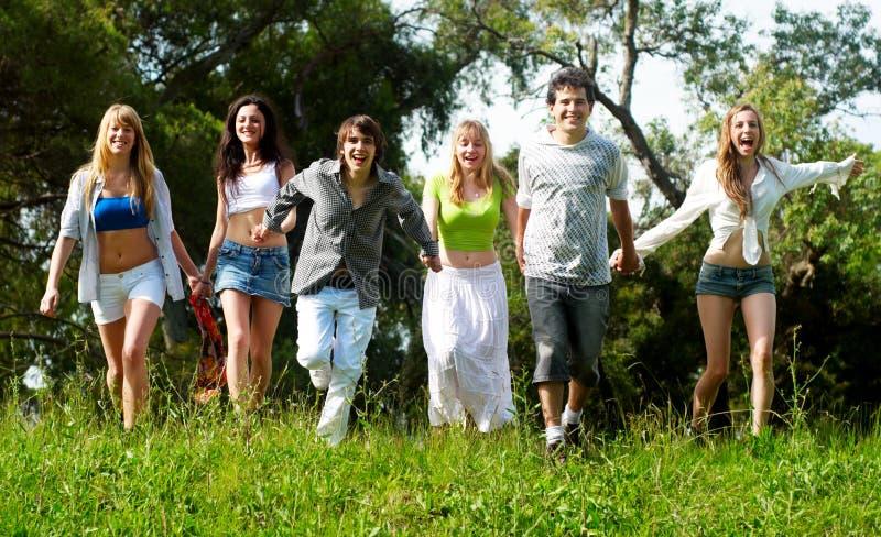 De groep die van de jeugd op een gras loopt stock foto's