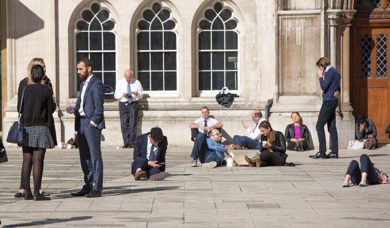 De Groep die van Londen, het UK mensen een rust hebben in lunchtijd in de Stad van de straat van Londen stock foto's