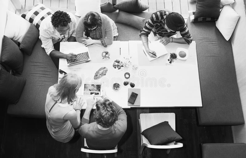 De groep diverse vrienden is brainstorming op hun project stock foto's