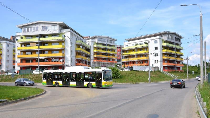 De groep gekleurde flatwoning huisvest, op kruispunt tegengehouden nieuwe stadsbus, het deel van stedelijk openbaar vervoer royalty-vrije stock afbeelding