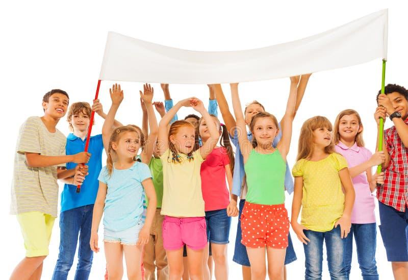 De groep gelukkige jonge geitjes houdt lege witte banner royalty-vrije stock foto