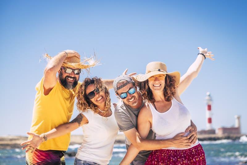 De groep gelukkige mensen en de vrolijke volwassenenvrienden hebben samen pret tijdens de vakantie van de de zomervakantie bij he stock afbeelding
