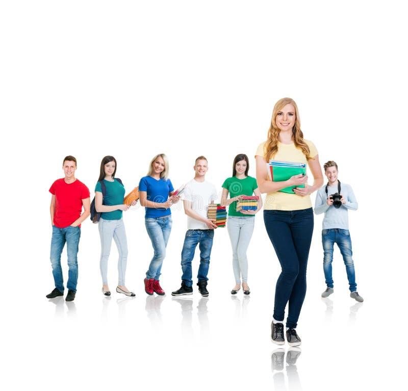 De groep gelukkige tieners met boeken iolsated op wit stock foto