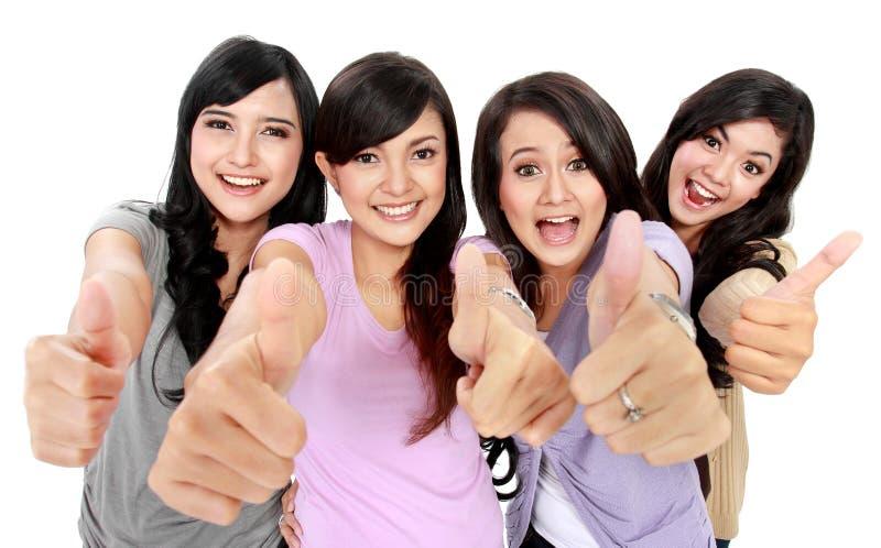 De groep het mooie vrouwen tonen beduimelt omhoog stock foto