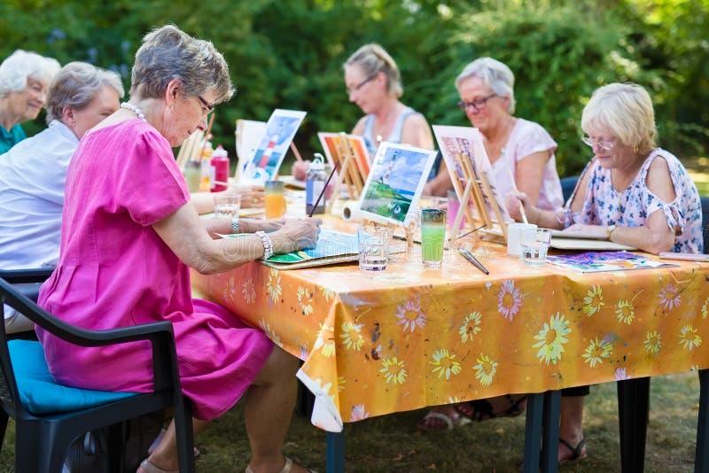 De groep hogere vrouwen die kunstlessen nemen die in openlucht bij één lijst zitten en samen leren hoe te beelden te schilderen royalty-vrije stock foto