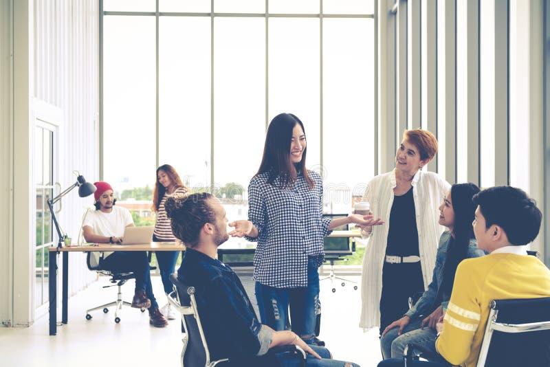 De groep jong multi-etnisch creatief team nam uitwisseling van ideeën in kleine vergadering in dienst terwijl status, zitting en  royalty-vrije stock afbeeldingen