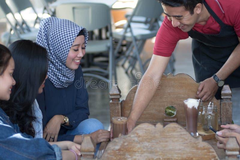 De groep jonge gelukkige vriend ontvangt voedsel en drank van kelners en server bij koffie en restaurant royalty-vrije stock fotografie