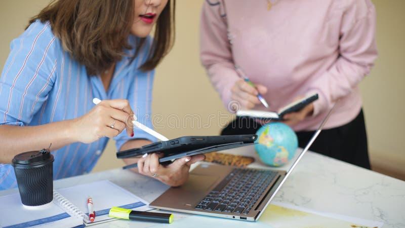 De groep jonge medewerkers is analyticsinformatie over laptop het scherm stock foto