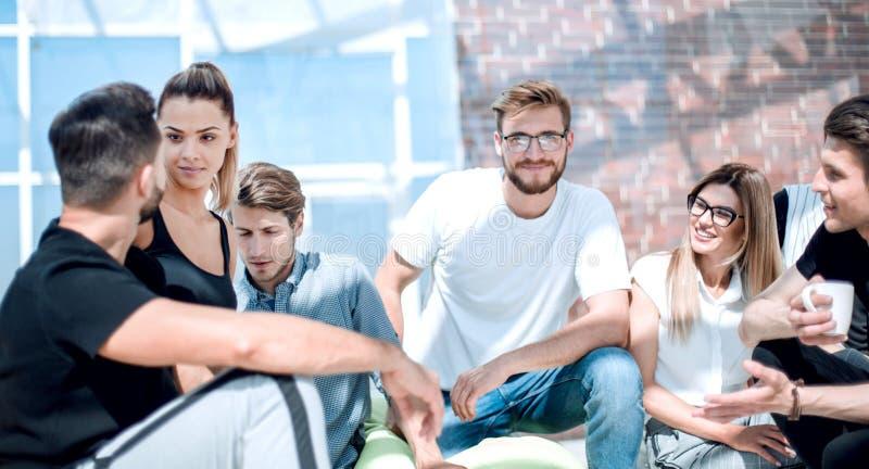 De groep jonge ondernemers zit op de vloer in het nieuwe bureau royalty-vrije stock foto's