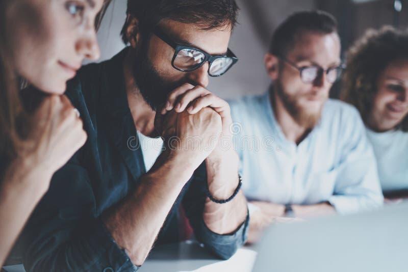 De groep jonge ondernemers zoekt een bedrijfsoplossing tijdens het werkproces op nachtkantoor Bedrijfs mensen stock afbeeldingen