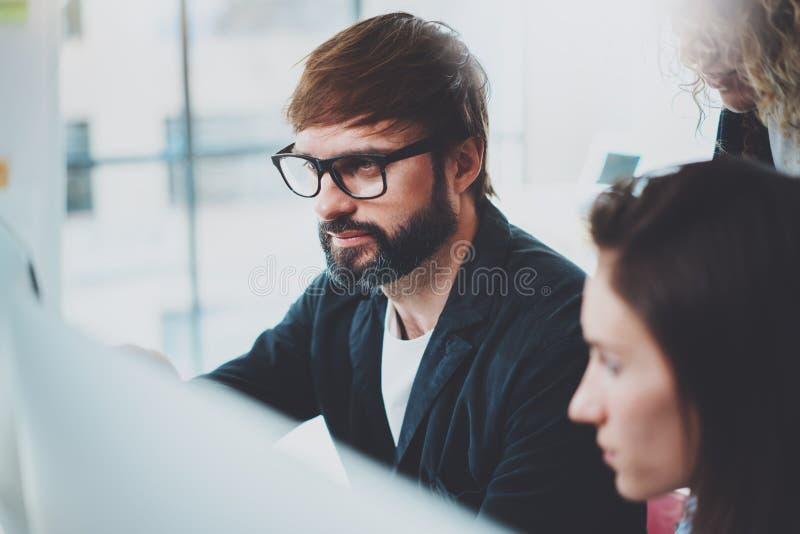 De groep jonge ondernemers zoekt een bedrijfsoplossing tijdens werktijd op zonnig kantoor stock fotografie