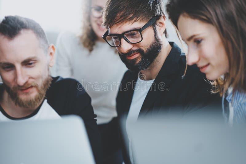 De groep jonge ondernemers zoekt een bedrijfsoplossing tijdens werktijd op zonnig kantoor Bedrijfs mensen stock afbeelding