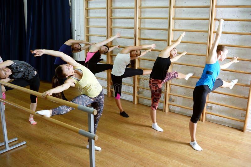 De groep jonge sportenvrouw doet een uitbreidingsoefening bij de Zweedse muur stock afbeelding