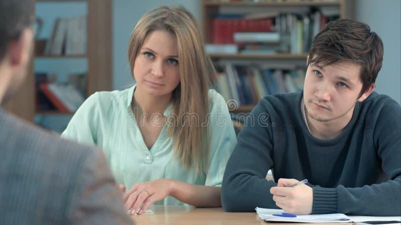 De groep jonge studenten die iets in hun nota schrijven vult terwijl het zitten op een rij bij hun bureaus op stock afbeelding