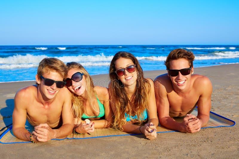 De groep jonge vrienden koppelt portret in strand stock foto