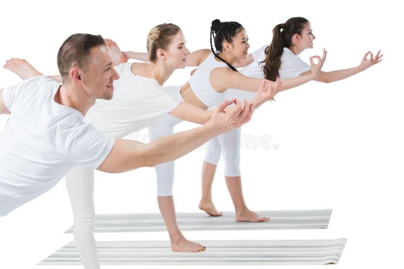 De groep jonge vrouwen met trainer status in Natarajasana-yoga stelt stock afbeeldingen