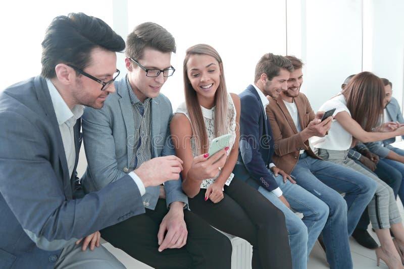 De groep jongeren gebruikt hun smartphones stock foto's