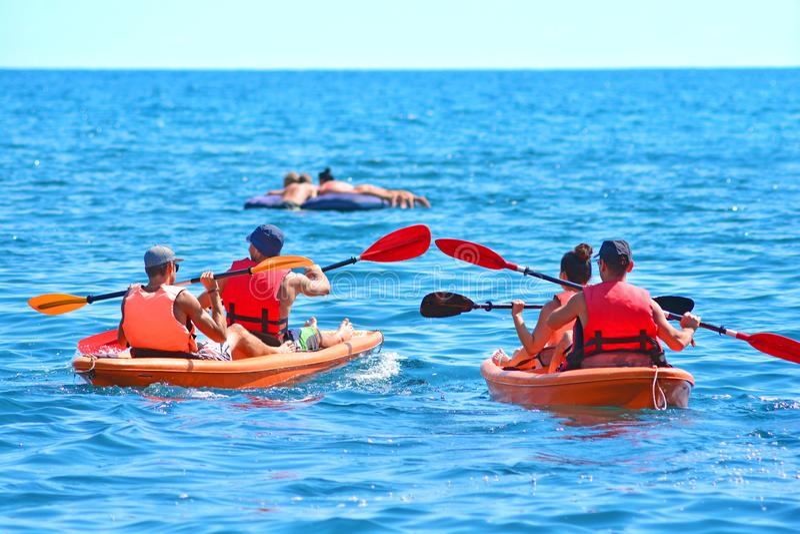 De groep kajaks zwemt door het overzees Kayakingsachtergrond royalty-vrije stock afbeeldingen
