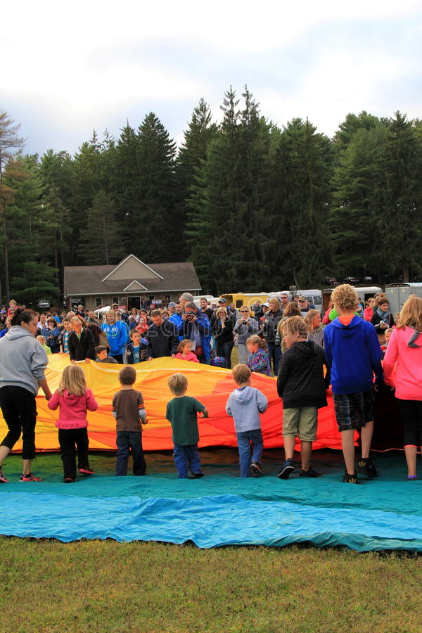 De groep kinderen en jonge volwassenen die ballons bij jaarlijks festival helpen te ontwikkelen, Crandall-Park, Nauwe valleien va royalty-vrije stock foto