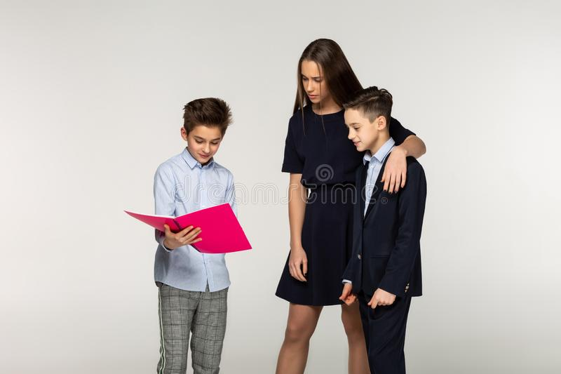 De groep kinderen heeft pret terwijl samen het doen van thuiswerk stock foto