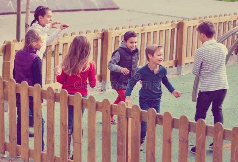 De groep kinderen het spelen stoeit in openlucht aanraking-Laatste spel stock afbeelding