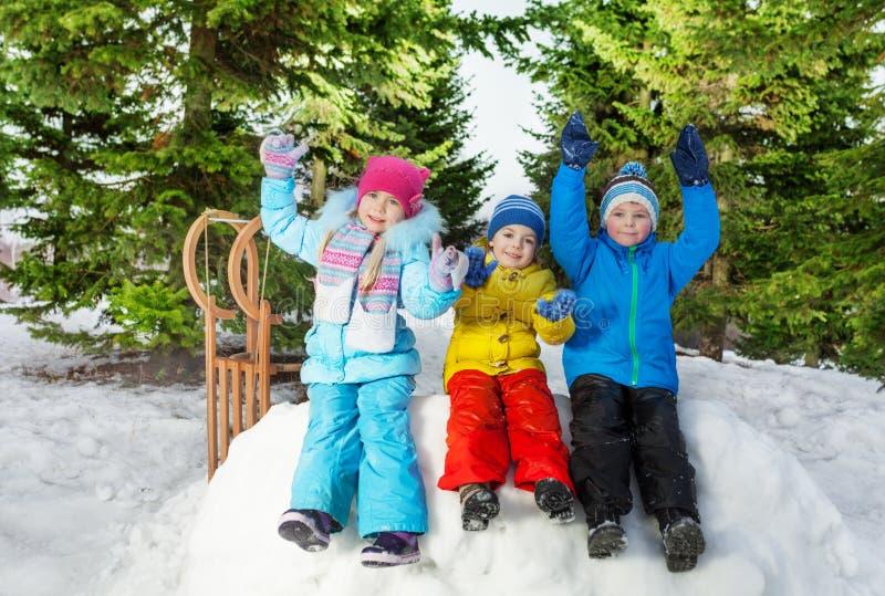 De groep kleine jonge geitjes zit op sneeuwmuur in park royalty-vrije stock foto's