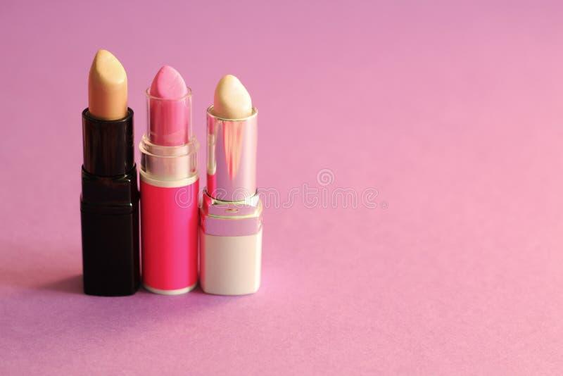 De groep lippenstiften, poedert roze achtergrond, vrije exemplaarruimte stock fotografie