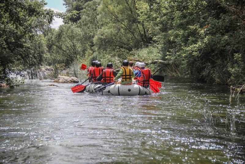 De groep mannen en vrouwen, geniet water van rafting activiteit bij rivier royalty-vrije stock fotografie