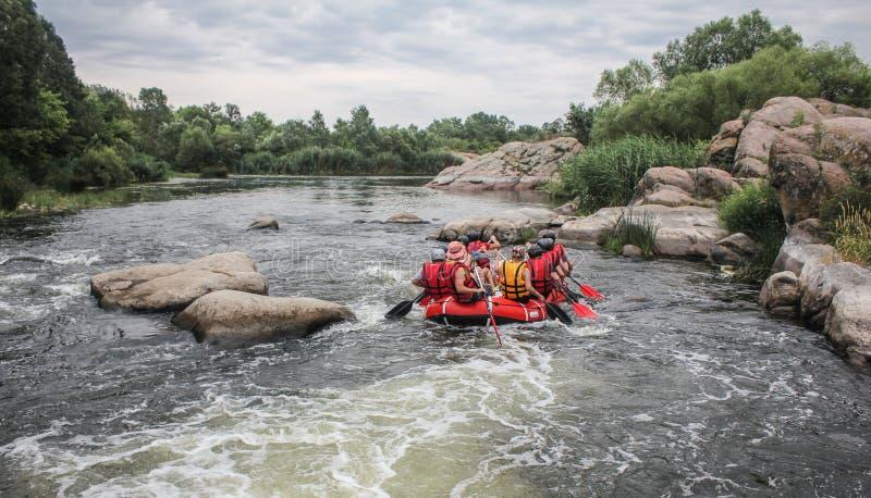 De groep mannen en vrouwen, geniet water van rafting activiteit bij rivier stock foto