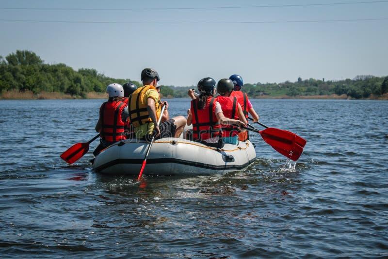 De groep mannen en vrouwen, geniet water van rafting activiteit bij rivier royalty-vrije stock afbeelding